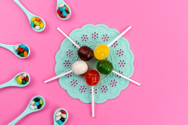 A top view colored lollipops with colorful candies on pink