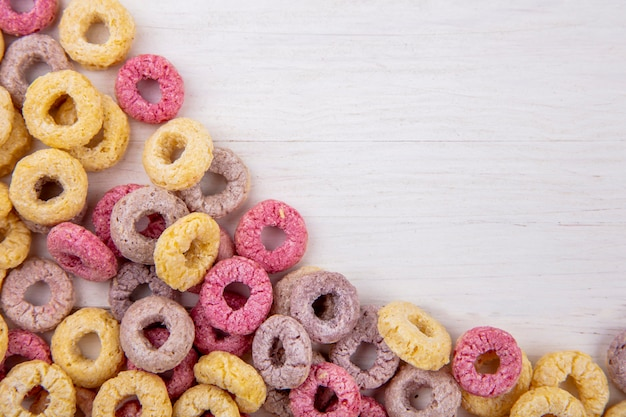 Top view of colored loop cereals on white with copy space
