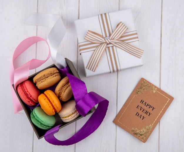 Top view of colored macarons in a box with colored bows and a gift box with a book on a white surface