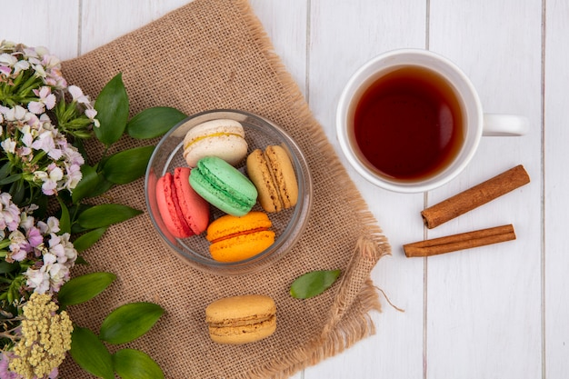 Top view of colored macarons in a jar with flowers and a cup of tea with cinnamon on a white surface
