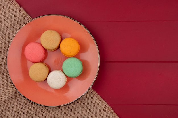 Top view of colored macarons on an orange plate on a beige napkin on a red surface