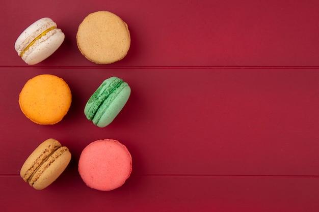 Vista dall'alto di macarons colorati su una superficie rossa