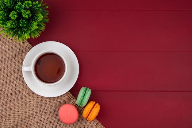 Top view of colored macarons with a cup of tea on a beige napkin on a red surface
