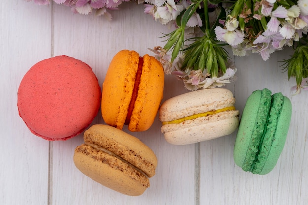 Top view of colored macarons with flowers on a white surface