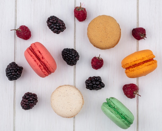 Top view of colored macarons with raspberries and blackberries on a white surface