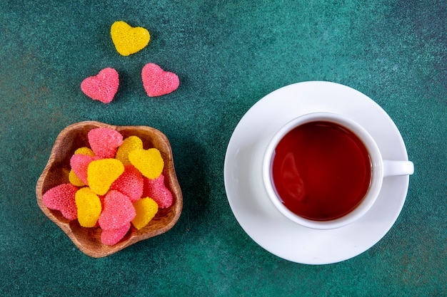Top view colored marmalade in the form of a heart with a cup of tea on green