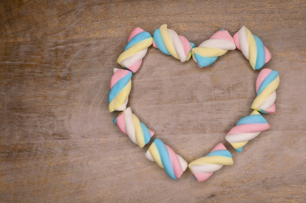 Top view on colored marshmallows candies on wooden background concept of sweet food and desserts heart shape