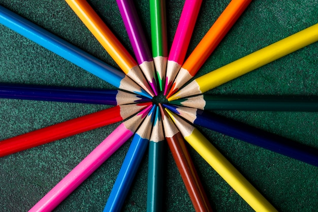 Top view of colored pencils arranged on dark