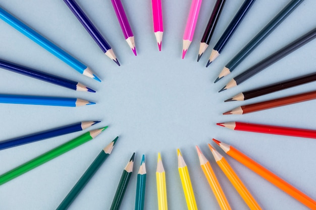 Top view of colored pencils arranged on white