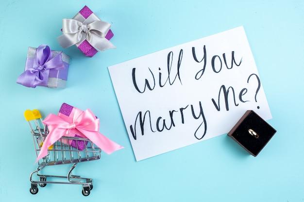 Вид сверху цветные маленькие подарки тележка для мини-маркета «выйдешь ли ты за меня замуж» написано на бумажном кольце в коробке на синем фоне