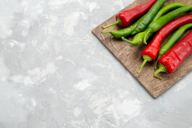 Top view colored spicy peppers green and red on grey desk