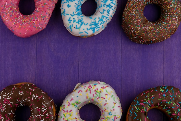 Top view of colored sweet donuts on a bright purple surface