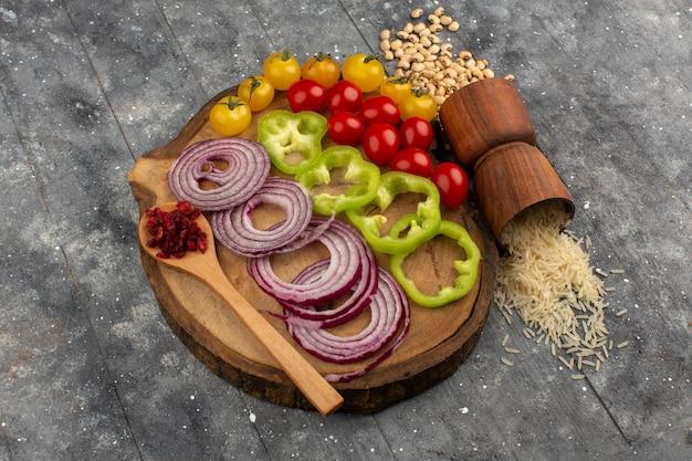 グレーの茶色の木製の机の上の平面図色野菜スライスと全体の野菜
