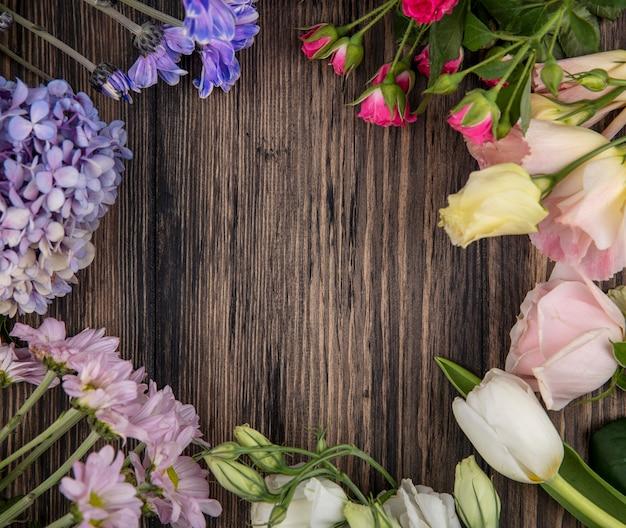 Vista dall'alto di fiori colorati sorprendenti come la margherita delle rose lilla con foglie su uno sfondo di legno con spazio di copia