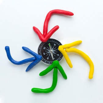 Top view of colorful arrows pointing at compass