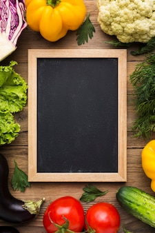 Top view colorful background with vegetables and blackboard