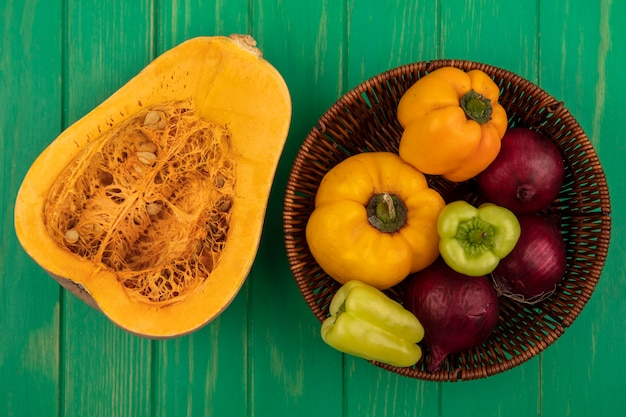 Top view of colorful bell peppers on a bucket with red onion with pumpkin isolated on a green wooden wall