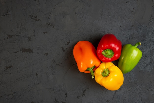 Top view of colorful bell peppers with copyspace on dark