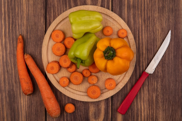 Top view of colorful bell peppers on a wooden kitchen board with chopped carrots with knife with carrots isolated on a wooden surface