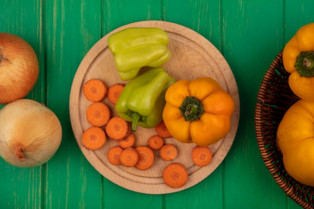Top view of colorful bell peppers on a wooden kitchen board with chopped carrots with onions isolated on a green wooden wall