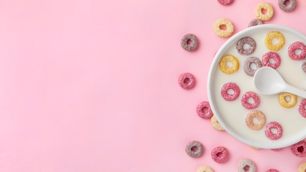 Top view of colorful breakfast cereals with copy space and milk