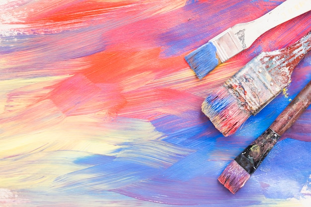 Top view of colorful brushstroke and dirty paint brushes