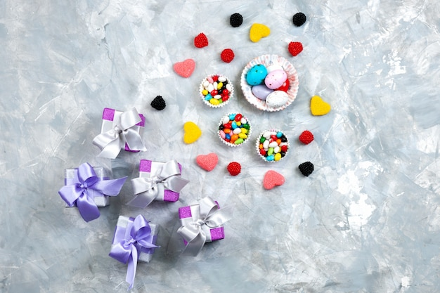 A top view colorful candies along with heart shaped marmelades little purple gift boxes bows on the grey background present celebration candy