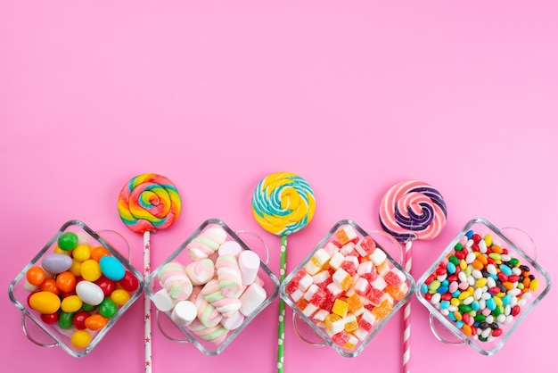 A top view colorful candies along with lollipops on pink desk