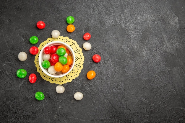 Top view colorful candies on a dark background color rainbow sweet tea