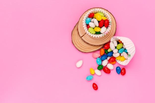 Una vista dall'alto caramelle colorate deliziose diverse colorate isolate sul rosa