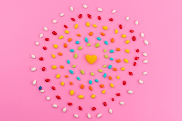 A top view colorful candies forming a circle on pink