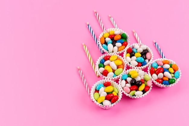 A top view colorful candies inside paper packages along with candles on pink