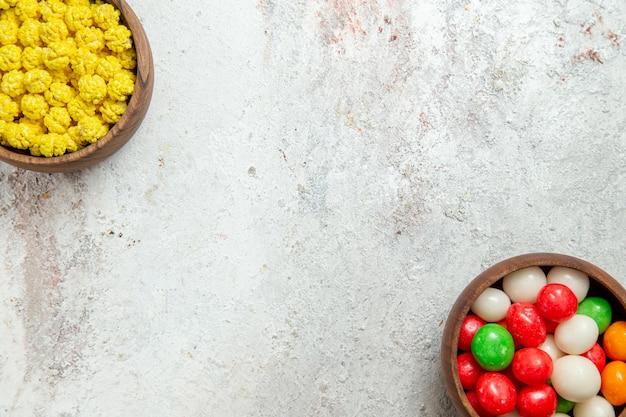 Vista dall'alto caramelle colorate sulla scrivania bianca zucchero candito color arcobaleno