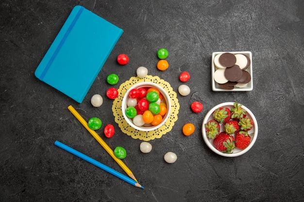暗い背景色の虹の甘い果物にクッキーとイチゴとカラフルなキャンディーの上面図