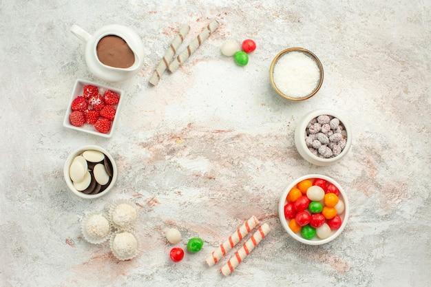 上面図白い背景の上のクッキーとカラフルなキャンディービスケット甘いケーキクッキー