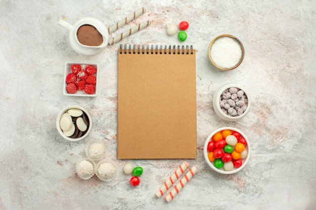 Top view colorful candies with cookies on white background color rainbow biscuit tea cake