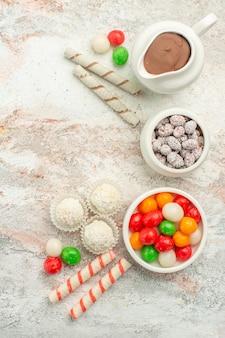 Vista dall'alto caramelle colorate con biscotti sulla torta di tè con biscotto arcobaleno colore scrivania bianca