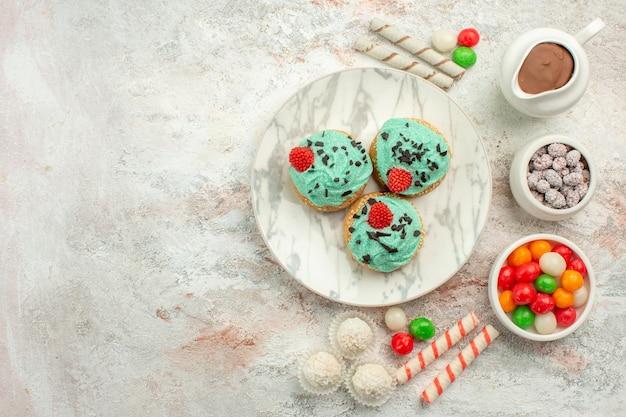 Caramelle colorate vista dall'alto con torte cremose su torta di tè biscotto arcobaleno colore superficie bianca