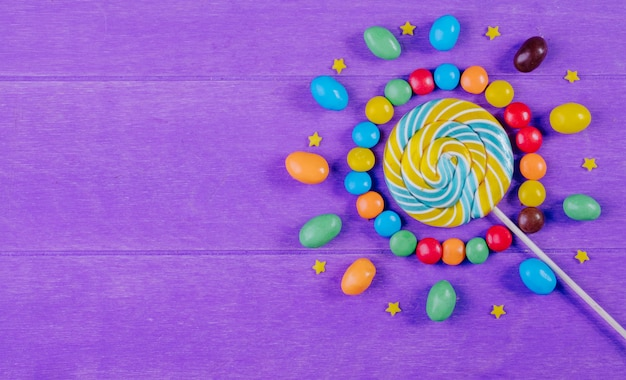 Top view of colorful candies with lollipop on purple wooden background with copy space