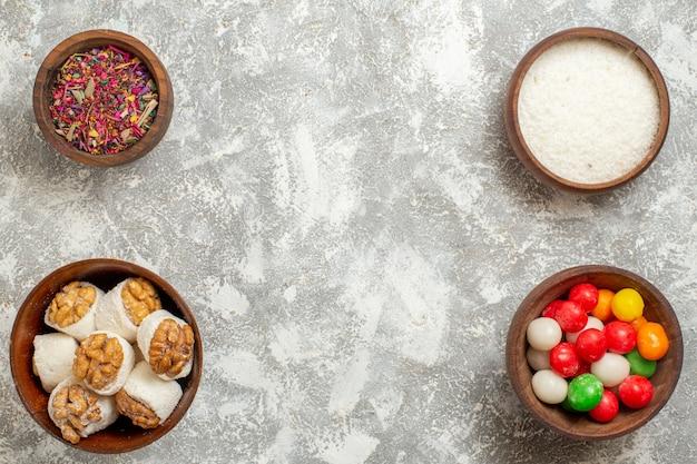 Caramelle colorate vista dall'alto con confetture di noci su un arcobaleno di caramelle di colore bianco chiaro