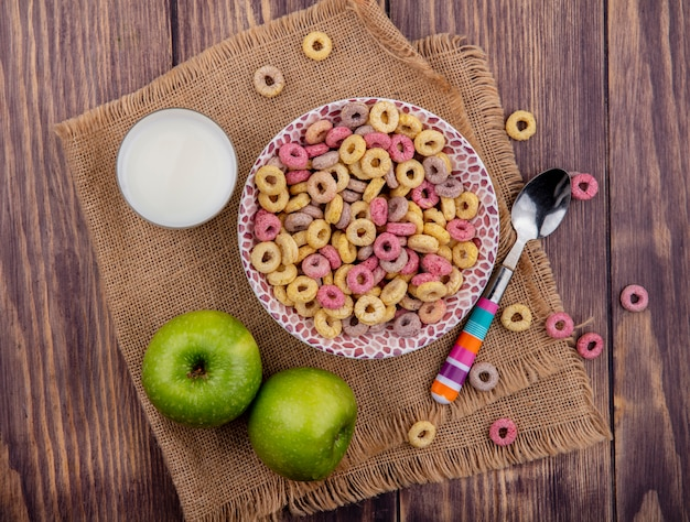 Top view of colorful cereals on bowl with spoon with apples and a glass of milk on sack cloth on wood