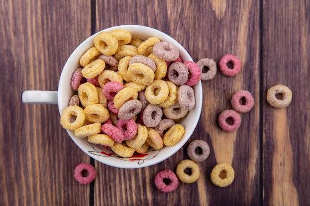 Top view of colorful cereals on cup with cereals isolated on wood