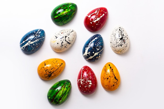 A top view colorful chocolate eggs designed isolated on the white wall