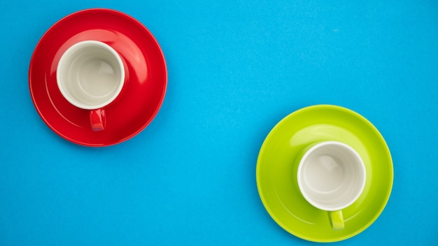 上面図青い紙の背景にカラフルなコーヒーカップ。