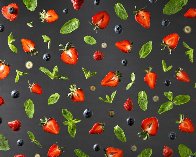Top view of colorful composition of strawberry red ripe, blueberry and green sprig of mint isolated