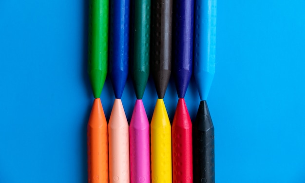 Top view colorful crayons lined up facing each other
