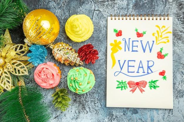 灰色の背景のノートに書かれた新年のトップビューカラフルなカップケーキ