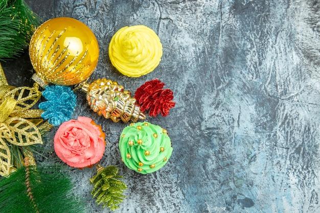 Vista dall'alto cupcakes colorati ornamenti di natale su sfondo grigio