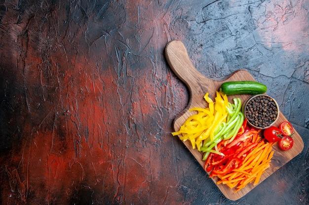 Vista dall'alto colorato peperoni tagliati pepe nero pomodori cetriolo sul tagliere sul tavolo rosso scuro con lo spazio della copia