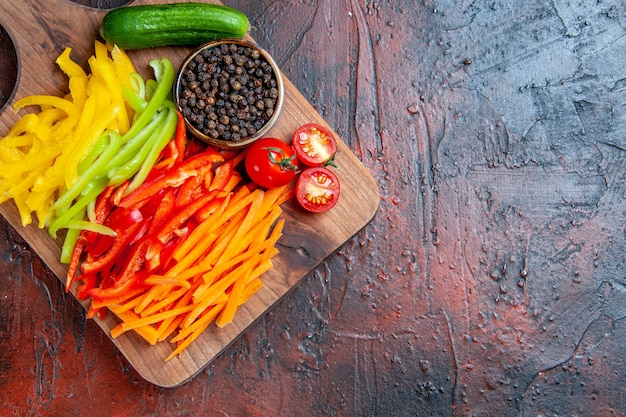 Top view colorful cut peppers black pepper tomatoes cucumber on chopping board on dark red table with copy space
